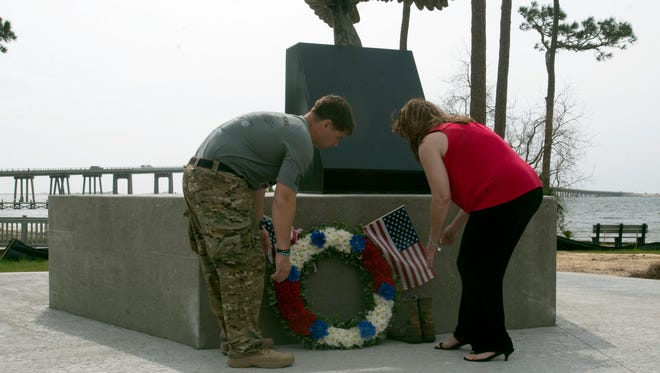 Nathan Harris, left, and Michele Tucker, right, lay a wreath at the base of the Navarre Blackhawk Memorial during a ceremony in Navarre Friday morning March 11, 2016.