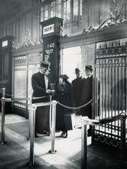 A conductor checks a passenger's ticket at the Michigan