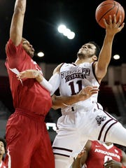 Mississippi State guard Quinndary Weatherspoon (11) attempts a layup past an Arkansas defender during the first half of their NCAA college basketball game in Starkville, Miss., Tuesday, Jan. 2, 2018. (AP Photo by Rogelio V. Solis)