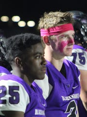 Seniors Chris Jamison (left) and Ty Slazinski watch the action in Friday's wild game against Oak Park where the teams scored a combined 97 total points.
