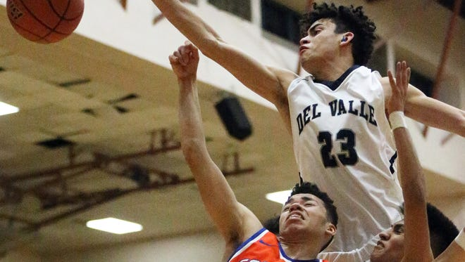 Alex Monreal, 20, of Canutillo gets the ball deflected by Del Valle's Julian Najera, 23, and Jesse Martinez, as he drove for the basket Tuesday night at Del Valle.