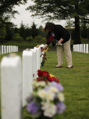 """Ami Neiberger-Miller places flowers at the gravesite of Sean Hugo at Arlington National Cemetery. """"There is a sense of taking care of each other here"""" Neiberger-Miller said about placing flowers at different soldier's gravesites.   USA T 4/30/12 2:29:15 PM -- Arlington  Ami Neiberger-Miller places  flowers at the grave site of Sean Hugo at Arlington National Cemetery.   """"There is a sense of taking care of each other here"""" Ami said about placing flowers at different soldier's grave sites.    -- ORGAN DONATION -- Dozens of brain-dead U.S. casualties whose life systems were kept alive until they were flown out of war zones to a U.S. Army hospital in Germany have become organ donors saving an estimated 100 European lives since 2006. The program, which is done in collaboration with a German organ donation group, allows for the harvesting of up to seven vital organs -- the heart, lungs, kidneys, liver and pancreas. The decision whether to remove the organs is left up the service member's next of kin who are allowed the opportunity to be flown to Germany in order to achieve emotional closure with the loss of their loved one. Medical officials then delicately raise the issue of organ donation. Battlefield medical guidelines issued in 2010 helped to ease the process for physicians on the frontlines who sometimes struggled with the dilemma of whether to keep alive a service member who has suffered a massive head wound and shows no signs of brain activity. The guidelines recommend that live systems are maintained until the service member reaches Germany and families can arrive, and organ donation is possible --    Photo by Garrett Hubbard, USA TODAY staff"""