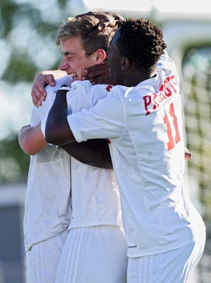 Lincoln forward Isaac Woods (21) celebrates with teammates, including David Bizimana (11), after scoring the first goal of the game during the Class AA state championship semifinal match Tuesday, Oct. 3, 2017, at Howard Wood Field in Sioux Falls. Lincoln defeated Rapid City Central 4-1.