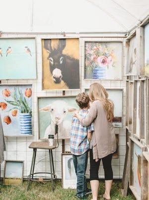 A mother and son  peruse art at a City Farmhouse pop-up fair.