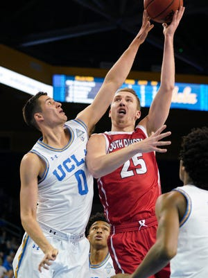South Dakota Coyotes forward Tyler Hagedorn (25) attempts a shot defended by UCLA Bruins forward Alex Olesinski (0) during the second half at Pauley Pavilion. Mandatory Credit: Kelvin Kuo-USA TODAY Sports