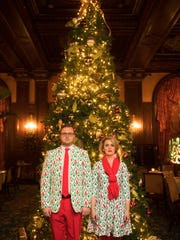 Amy Watson Bish and Andrew Truscott wearing matching Ugly Christmas Reindeer outfits from Shinesty.com in front of the Christmas tree at Hotel DuPont.