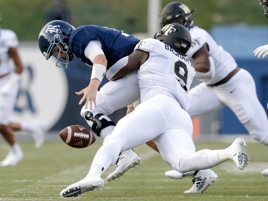 HOUSTON, TX - SEPTEMBER 06:  Carlos Basham Jr. #9 of the Wake Forest Demon Deacons sacks Wiley Green #5 of the Rice Owls forcing a fumble in the first quarter on September 6, 2019 in Houston, Texas.  (Photo by Tim Warner/Getty Images)