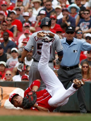 Cleveland Indians starting pitcher Carlos Carrasco (59) tags up at first as Cincinnati Reds first baseman Joey Votto (bottom) goes for the ball.