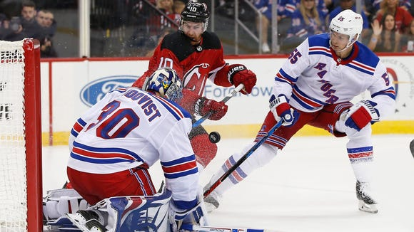 New Jersey Devils right wing Jimmy Hayes (10) takes a shot that sails over New York Rangers goalie Henrik Lundqvist (30), of Sweden, as Rangers' defenseman Nick Holden (55) defends during the second period of a preseason NHL hockey game in Newark, N.J., Saturday, Sept. 23, 2017.