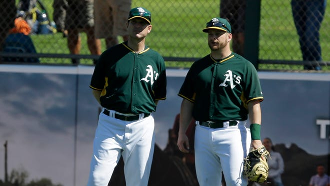 Michigan football coach Jim Harbaugh, left, talks with Oakland Athletics' Stephen Vogt as the Athletics take batting practice March 7, 2015.