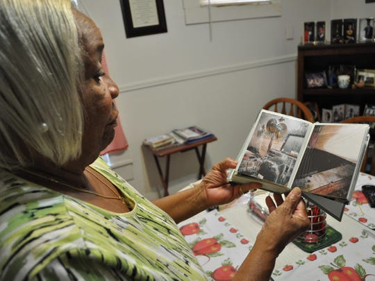Celia Harris holds a photo album with images of her New Orleans home, which was flooded after Hurricane Katrina.