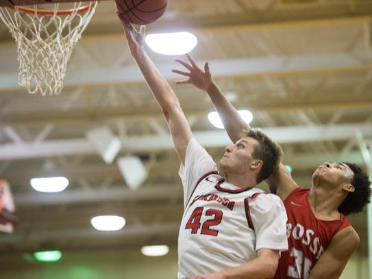 Harrison's Rilee Epley (42) goes up for a layup over Bosse's Donovan McNeal (30) at Harrison High School on Tuesday, Feb. 13, 2018.