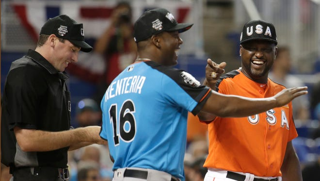 U.S. Team's manager Charles Johnson, right, talks with World Team's manager Edgar Renteria (16) during the All-Star Futures baseball game, Sunday, July 9, 2017, in Miami. (AP Photo/Lynne Sladky)