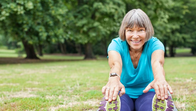 Portrait of fit elderly woman doing stretching exercise on yoga mat in park