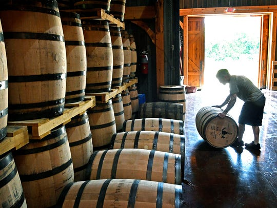 Rainey Kirk, director of proofing, rolls a barrel into