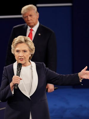 In this Oct. 9, 2016 file photo, Republican presidential nominee Donald Trump listens to Democratic presidential nominee Hillary Clinton during the second presidential debate at Washington University in St. Louis. Clinton has a lot of plans for 2017, including some reflections on her stunning loss to Trump. The former secretary of state, senator and first lady is working on a collection of personal essays that will touch upon the 2016 presidential campaign, Simon & Schuster told The Associated Press on Feb. 1, 2017. The book, currently untitled, is scheduled for this fall 2017 and will be inspired by favorite quotations she has drawn upon.