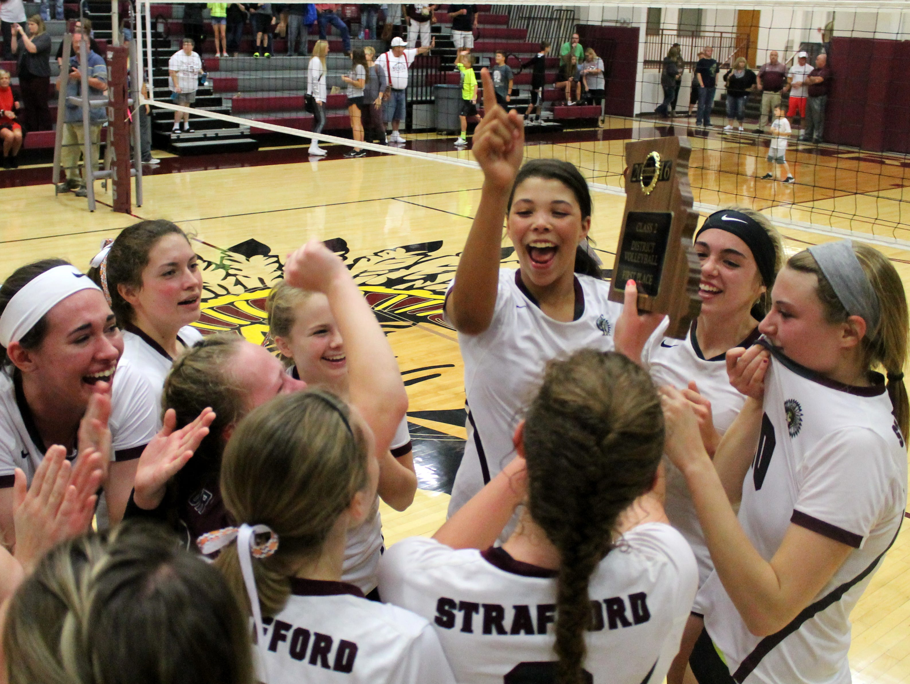 The Strafford High School volleyball team celebrates with the 2016 Class 2 District 12 championship trophy.