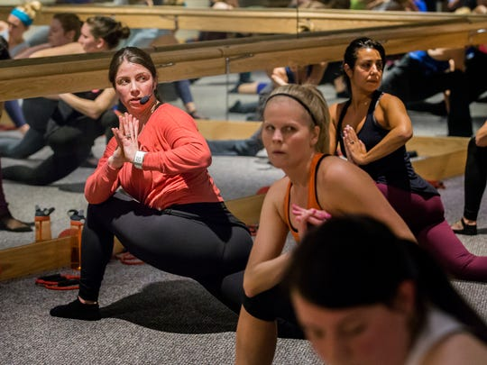 Maura Markley (left), owner of Pure Barre Greenville, demonstrates proper form as she leads a class on Wednesday, March 30, 2016.