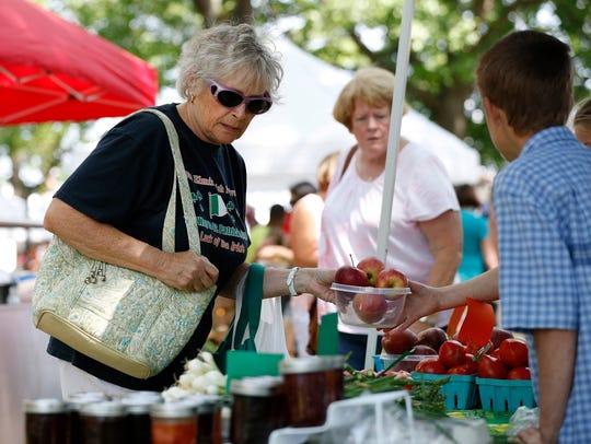 Carol Ellis, of West Elmira, picks up fresh apples
