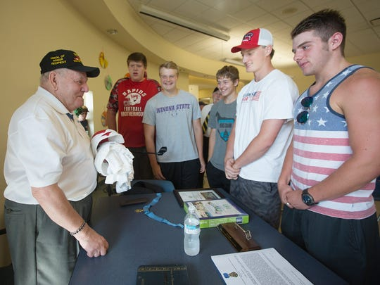 Vietnam War veteran and Medal of Honor recipient Ken Stumpf receives T-shirts and hats from members of the Lincoln High School football team during the American Heroes Cafe on Wednesday at the Lowell Senior Center in Wisconsin Rapids.