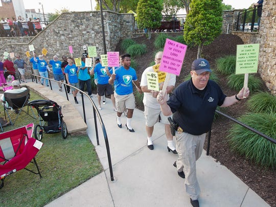 Anderson Police Department Lt. Don Hodges leads a group of men wearing high heel shoes during the Foothills Alliance Walk A Mile in Their Shoes event at the Block Party in downtown Anderson on Thursday. The walk raises awareness about sexual assault and the group serving Anderson and Oconee Counties.