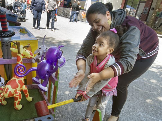 Jorgina Feliciano, top, of York, helps her daughter Yasmin Washington, age 3, win a prize during the 41st Annual Olde York Street Fair in York Sunday May 8, 2016