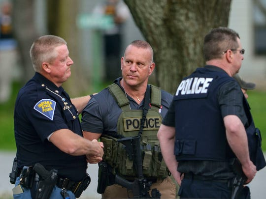 Indiana State Police Sgt. Joe Watts, left, consoles Terre Haute Chief of Police John Plasse, center, at the scene of a fatal shooting of a Terre Haute police officer at an apartment building Friday, May 4, 2018, in Terre Haute, Ind. An Indiana officer was killed Friday evening in an exchange of gunfire between police and a homicide suspect, who barricaded him inside an apartment complex and later died from injuries sustained during the shootout, authorities said.