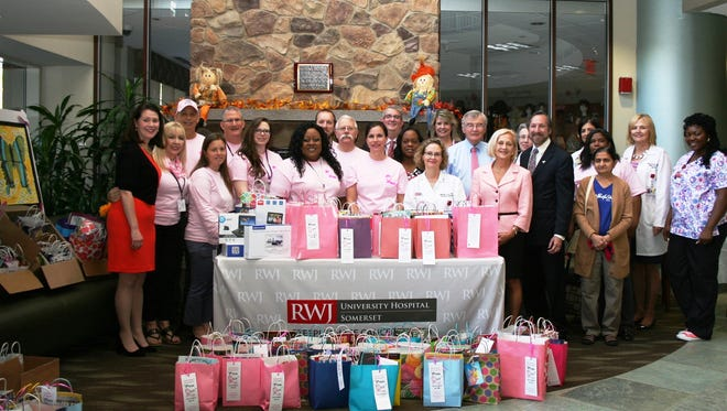 "Somerset County employees and RWJ Steeplechase Cancer Center physicians, staff and volunteers are pictured with Freeholder Director Patricia L. Walsh (fifth from the right) and Freeholder Deputy Director Peter S. Palmer and Freeholder Brian D. Levine (behind her, left to right) at the fourth annual ""Pink Out"" presentation of donated items for patients and caregivers at the medical center."