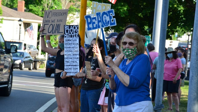 """People lined the streets of Middleton in front of the Flint Public Library during """"Middleton Has a Voice"""" on June 5."""
