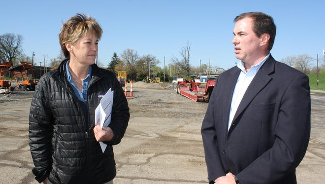 Nancy Wood, spokeswoman for Kentucky Transportation Cabinet's District 6 Department of Highways, and Chief District Engineer Rob Hans discuss summer road projects expected to significantly affect traffic in Newport where a new roundabout will be constructed. The roundabout will connect a new extension of Ky. 9 with the Fourth Street bridge across the Licking River to Covington in the background.