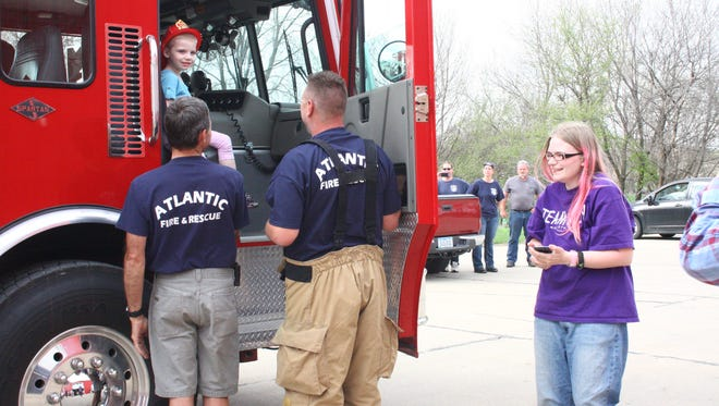 Leatha Slauson is shown standing at right next to an Atlantic Fire Department fire truck in April 2014 when her daughter, Riley, sitting in the truck, was named a firefighter for the day. The fire volunteers and town at the time believed that Riley was dying from cancer. Slauson has since been arrested and accused of faking her daughter's illness to raise money.