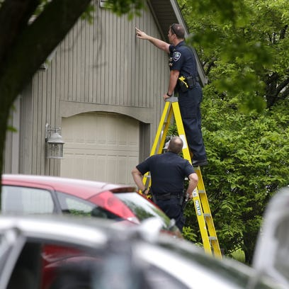 Police officers look for stray bullets in the 900 block of South Kensington Drive Saturday after shooting on Appleton's east side. Police said a 23-year-old Appleton man attacked a police officer, took her handgun and shot her and a Good Samaritan before killing himself.