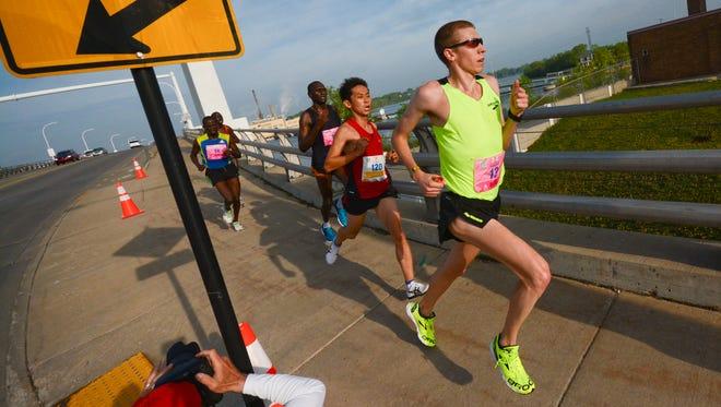 Matt Barrett of Verona, right, and Masashi Shirotake of Charlotte, N.C., second from right, lead runners across the De Pere bridge during the Cellcom Green Bay Marathon on Sunday, May 17, 2015.