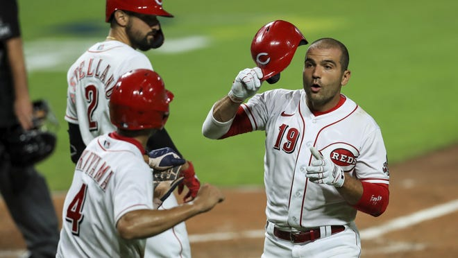 Cincinnati Reds' Joey Votto (19) is congratulated by teammates after hitting a two-run home run in the sixth inning of the team's baseball game against the Cleveland Indians in Cincinnati, Monday, Aug. 3, 2020.