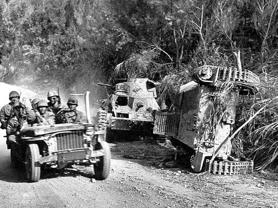 Soldiers drive past destroyed tanks on Saipan.