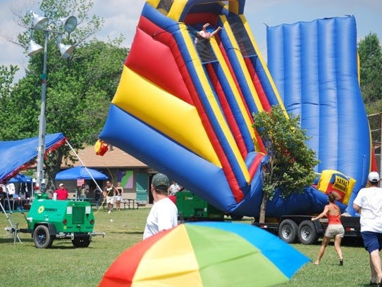 An inflatable slide blows over with a person inside