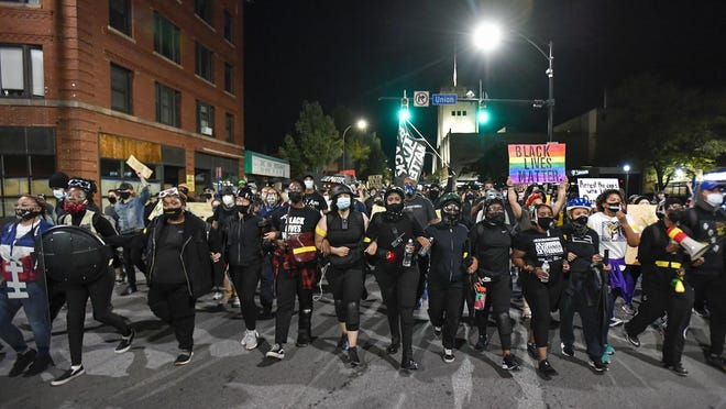 Demonstrators march through the streets Friday in Rochester while protesting the death of Daniel Prude. Prude apparently stopped breathing as police in Rochester were restraining him in March 2020 and died when he was taken off life support a week later.