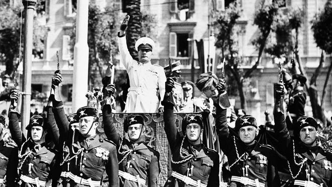 Benito Mussolini in Rome June 5, 1939 as he gives the Fascist salute as he reviews detachments of the Italian Carabibieri, the military police, celebrating their 125th anniversary. The dictator is surrounded by his bodyguard, with daggers raised.
