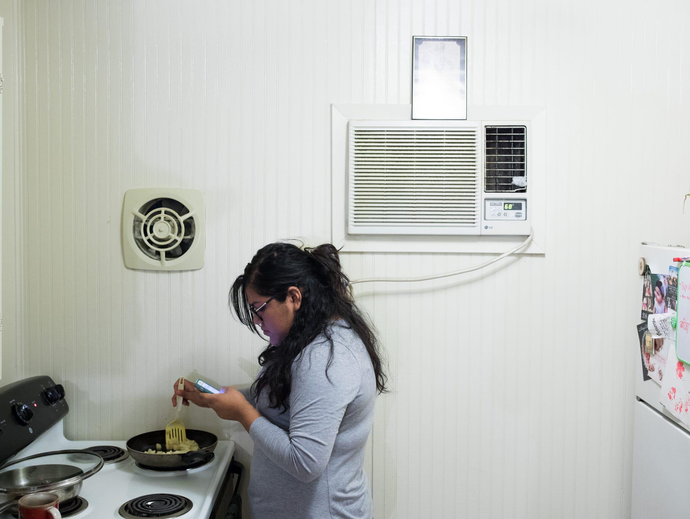 Maria Hernandez cooks breakfast in her apartment in