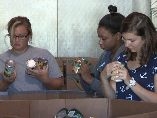 PSC students, from left, Ashton Sanderson, Kendra Davis, and Caitlin Hattaway learn through service at Manna.