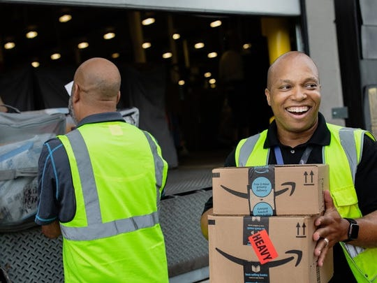 Amazon.com employees unloading a truck