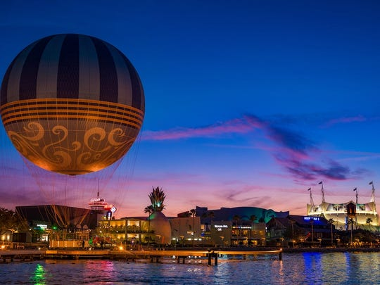 Panoramic view of Disney Springs across the lake as dusk takes over.