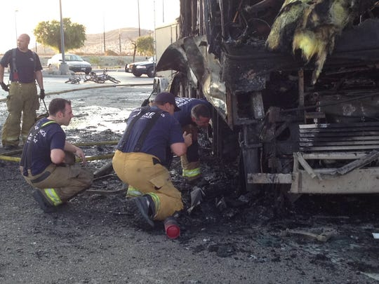 Palm Springs firefighters investigate a motor home that was destroyed in a fire at a Chevron gas station at Indian Canyon Drive and Garnet Avenue Thursday morning. A family of five was inside, but no one was injured.