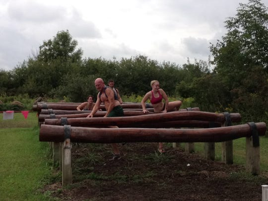 Participants climb one of many log obstacles on the course during the Swampfoot 4 Mile at Rattle Run Farms.