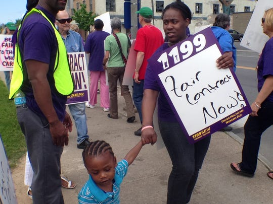 """Devery Reid-Holmes is led by son Daniel Martin during a picket Friday afternoon by 1199 SEIU at Unity Health System's St. Mary's Campus. Reid-Holmes is part of 1199 SEIU at Strong Memorial Hospital and came to Unity to """"support my sisters and brothers in our fight."""""""