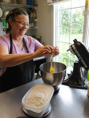 Cathy Berzins owner of Birch Tree Bakers & Lunch Cafe in Ocean View, a gluten-free bakery and lunch shop, mixes her bread dough.