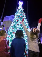 Children scream joyfully as the lights are turned on during the Christmas Tree Lighting in downtown Anderson.