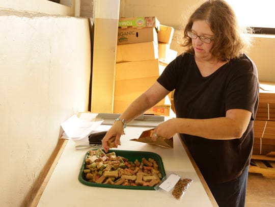 Luanne Pupeter packs dog treats for dog owners as a
