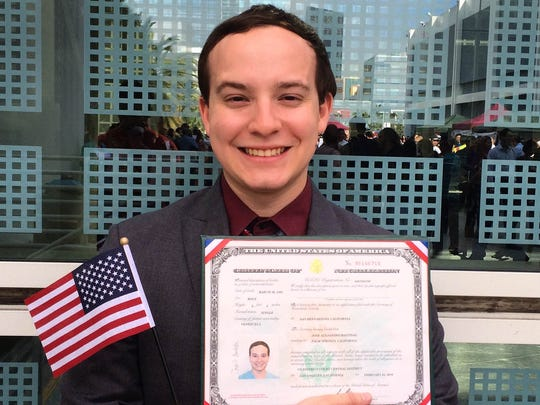 Content producer Jose A Bastidas poses with an American flag and his certificate of citizenship after a naturalization ceremony at the Los Angeles Convention Center on February 23, 2016.