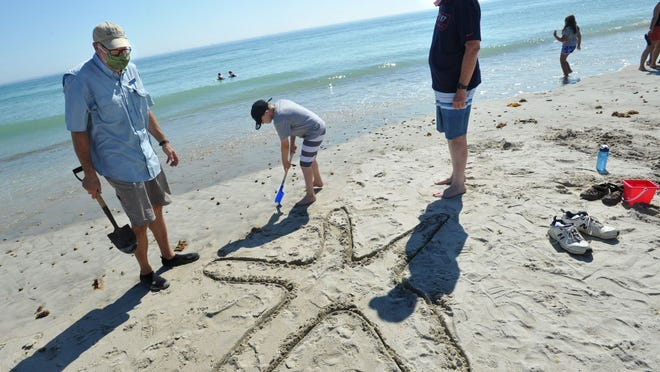Keagan Sciog, 10, of Plymouth, center, scoops a shovelful of sand to build his starfish sculpture as Mass Audubon's Doug Lowry, left, and Keagan's grandfather, Peter McMahon of Plymouth look on during the Mass Audubon and North River Wildlife Sanctuary sand sculpture program at Duxbury Beach on Saturday, July 18, 2020. Tom Gorman/For the Patriot Ledger
